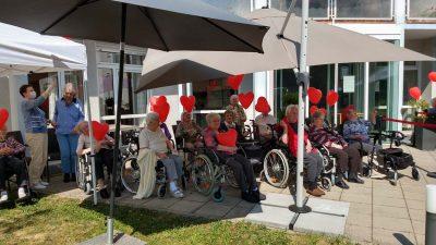 Senior*innen sitzen auf der Terrasse und haben rote Herz-Luftballons in den Händen.