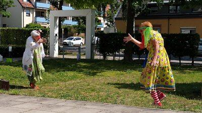 Zwei Clowninnen bei einem Auftritt im Garten.