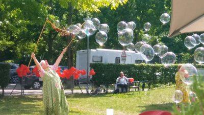 Eine Clownin macht riesen Seifenblasen im Freien.