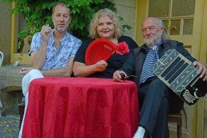Das Trio Nostalgia sitzt an einem Tisch und lächelt in die Kamera.