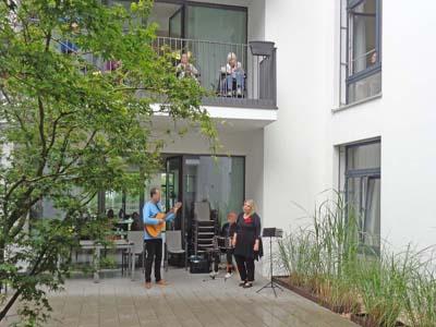 Das Trio Nostalgia steht im Innenhof des Seniorenzentrums Knielingen und macht Musik.