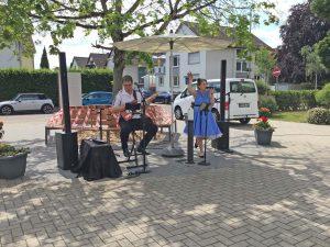 Eine Sängerin und ein Gitarrist geben ein Open Air Konzert im Hof eines Seniorenzentrums.