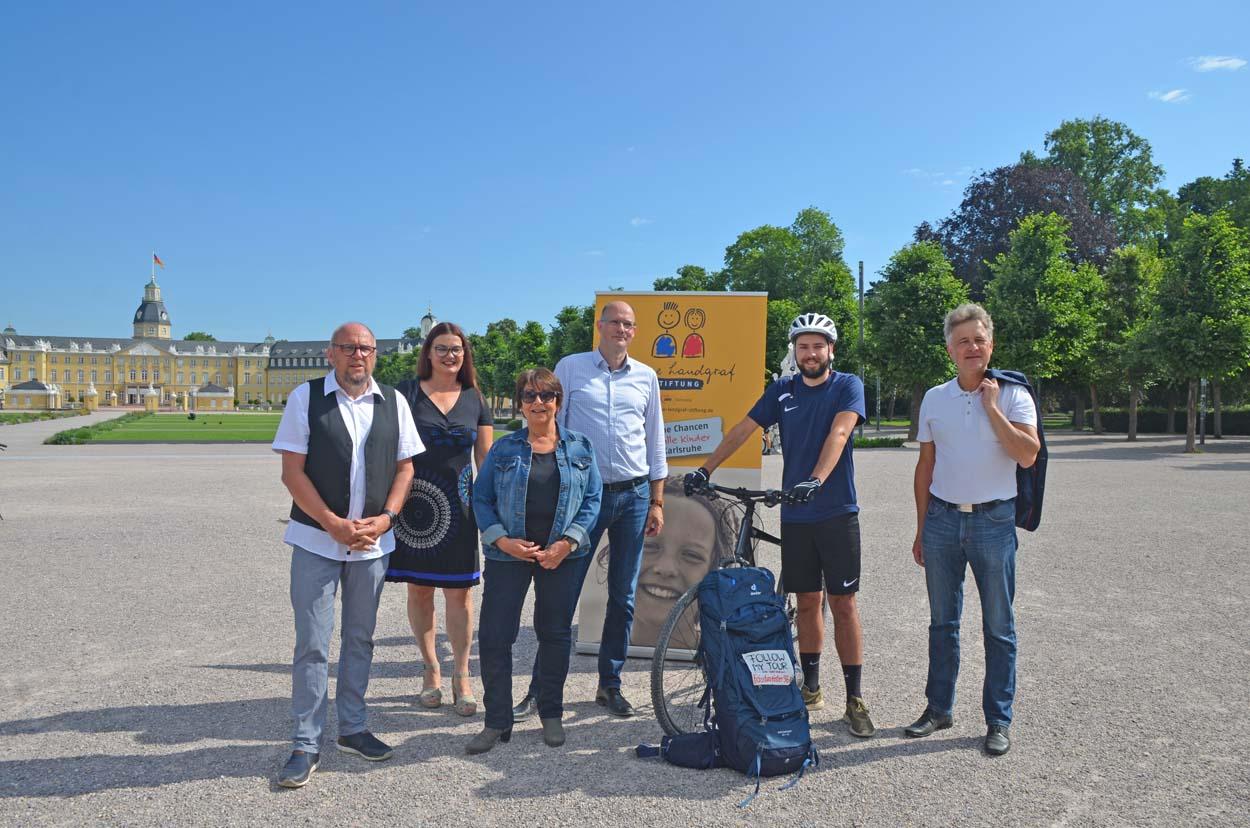 Eine Gruppe von Menschen steht vor dem Karlsruher Schloss.