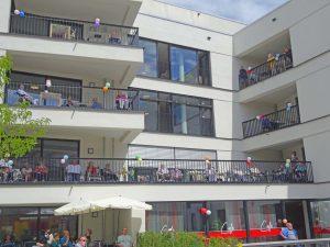 Senior*innen sitzen auf ihren Balkonen und winken.