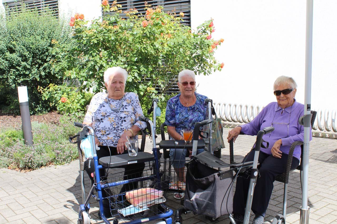 Drei Senior*innen sitzen im Freien und lachen.