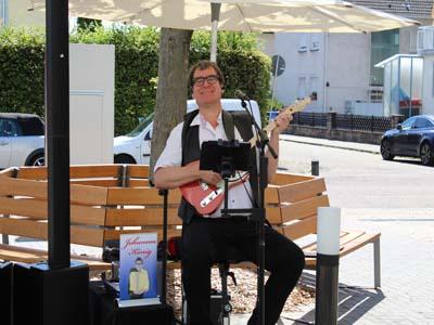Ein Mann sitzt mit einer Gitarre auf einer Bank.