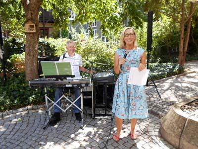 Eine Frau steht mit einem Mikro in der Hand vor einem Mann der an einem E-Piano sitzt.