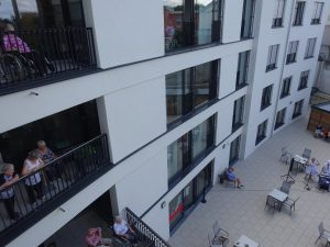 Senioren schauen aus dem Fenster des Anna-leimbach-Hauses und hören der Musik zu