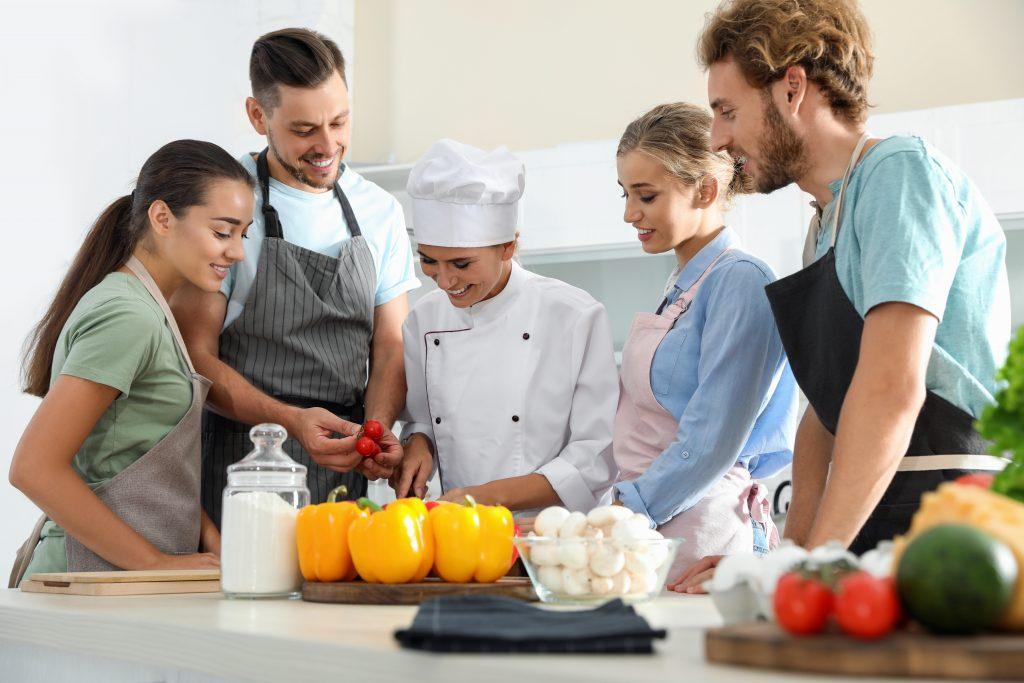Junge Menschen stehen in der Küche und bereiten etwas vor - Ausbildung