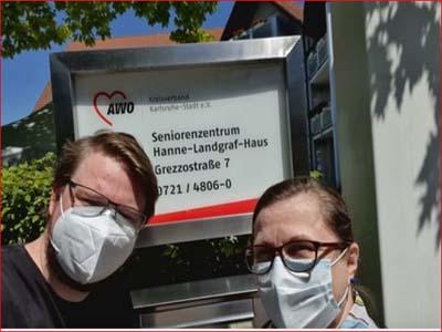Zwei Menschen mit Mundschutz stehen vor einem Schild auf dem steht Seniorenzentrumm Hanne-Landgraf-Haus