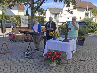 Drei Seniorinnen stehen draußen an einem Altar.