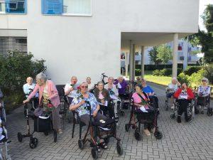 Seniorinnen und Senioren feiern unter freiem Himmel einen Gottesdienst.