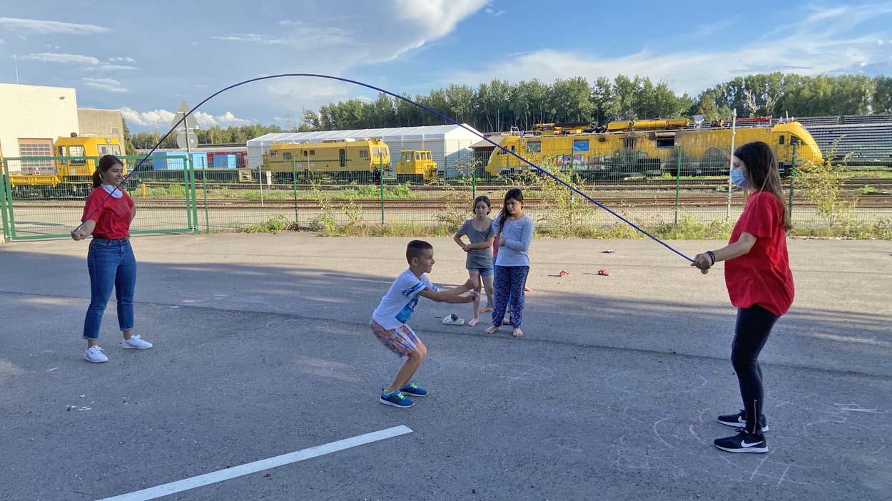 Zwei Kinder schwingen ein Seil und ein drittes Kind hüpft darüber.