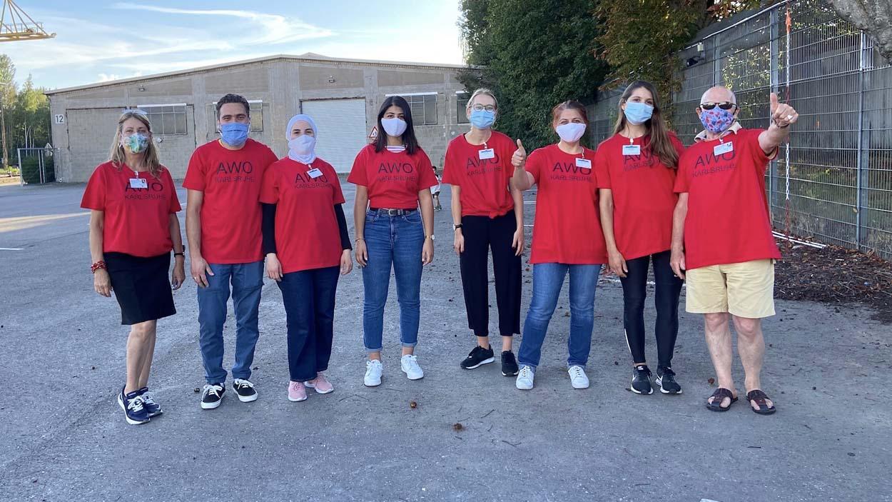 Acht Menschen in roten Tshirts und Masken stehen als Gruppe zusammen.