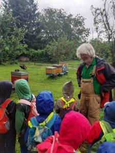 Kinder beim Imker vor den Bienenkästen