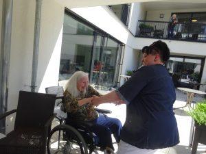 Betreuerin mit Bewohnerin im Rollstuhl